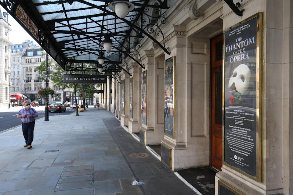 A man wearing a face mask walks past Her Majesty's Theatre in Haymarket, London, which used to show The Phantom Of The Opera before it closed because of the coronavirus pandemic. The Covid-19 crisis has wreaked havoc in the West End, where theatres have been dark since March.