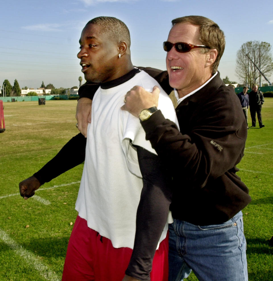FILE - In this Thursday, Jan. 10, 2002, file photo, San Francisco 49ers running back Garrison Hearst, left, is congratulated by 49ers general manager Terry Donahue during practice at the 49ers training camp in Santa Clara, Calif., as Hearst won The Associated Press NFL Comeback Player of the Year Award. Donahue, the winningest coach in Pac-12 Conference and UCLA football history who later served as general manager of the NFL's San Francisco 49ers, died Sunday, July 4, 2021. He was 77. (AP Photo/Paul Sakuma, File)