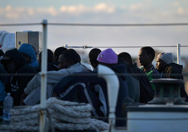 Illegal migrants sit on the Guardia Costiera boat after being rescued off the shores of the island of Lampedusa on October 25, 2013