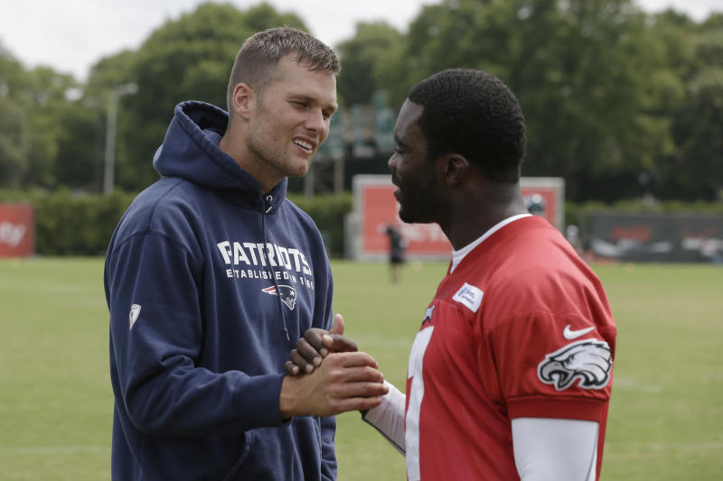 New England Patriots' Tom Brady, left, and Philadelphia Eagles' Michael Vick meet during a joint workout at NFL football training camp in Philadelphia, Thursday, Aug. 8, 2013. (AP Photo/Matt Rourke)