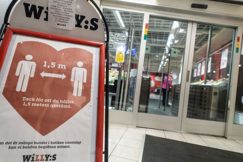 A sign reminding customers about social distancing is placed at the entrance to a grocery store in central Stockholm