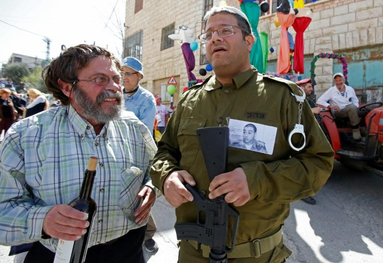 A Jewish settler dressed in military fatigues wears a portrait of Elor Azaria, an Israeli soldier who shot dead a wounded Palestinian assailant, during a parade marking the Jewish holiday of Purim in Hebron on March 12, 2017