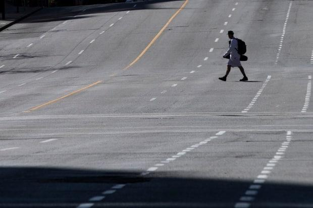 A man crosses an empty street in downtown Vancouver on April 14, 2020, during early COVID-19 lockdowns.  (Ben Nelms/CBC - image credit)