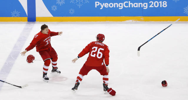 Russian athlete Kirill Kaprizov (77) and Vyacheslav Voynov (26) celebrate after winning the men's gold medal hockey game against Germany, 4-3, at the 2018 Winter Olympics, Sunday, Feb. 25, 2018, in Gangneung, South Korea. (AP Photo/Jae C. Hong)