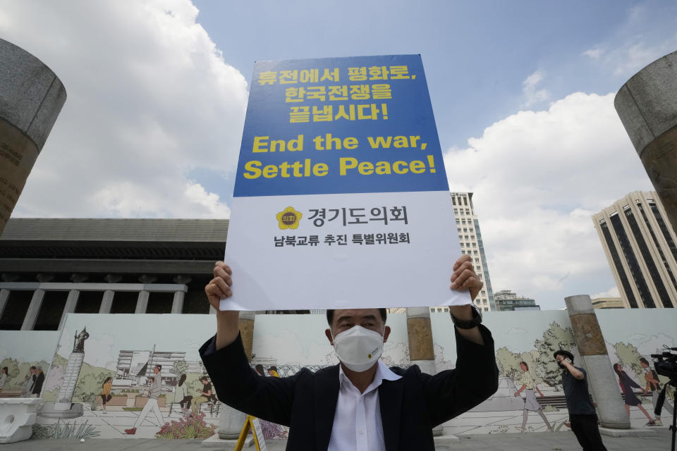 A man holds up a banner to demand the peace on the Korean peninsula near the U.S. Embassy in Seoul, South Korea, Tuesday, July 27, 2021. South Korea says the leaders of North and South Korea have agreed to restore suspended communication channels and improve ties. (AP Photo/Ahn Young-joon)
