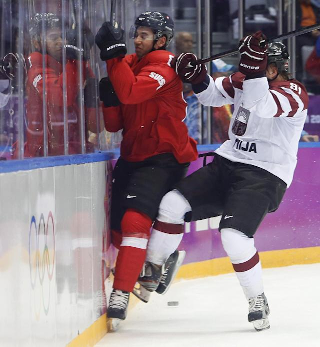 Latvia forward Ronalds Keninsm, right, checks Switzerland forward Simon Moser in the first period of a men's ice hockey game at the 2014 Winter Olympics, Tuesday, Feb. 18, 2014, in Sochi, Russia. (AP Photo/Mark Humphrey)