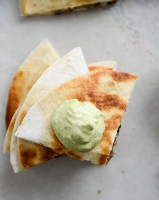 "<strong>Get the <a href=""http://www.howsweeteats.com/2013/02/cheesy-double-bean-quesadillas-with-homemade-avocado-ranch/"" rel=""nofollow noopener"" target=""_blank"" data-ylk=""slk:Cheesy Double Bean Quesadillas with Homemade Avocado Ranch recipe"" class=""link rapid-noclick-resp"">Cheesy Double Bean Quesadillas with Homemade Avocado Ranch recipe </a>from How Sweet It Is</strong>"