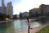 Michelle Rasul enjoys a run along a lake in Dubai, United Arab Emirates, Sunday, May 9, 2021. Rasul, a 9-year-old girl from Azerbaijan who lives in Dubai, is scratching her way to the top as a DJ after competing in the DMC World DJ Championship. (AP Photo/Kamran Jebreili)