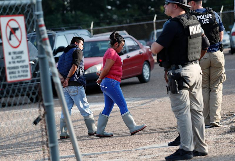 Two people are taken into custody at a Koch Foods Inc. plant in Morton, Mississippi on Aug. 7, 2019.