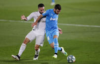 Real Madrid's Dani Carvajal, left, challenges for the ball with Valencia's Jose Luis Gaya during the Spanish La Liga soccer match between Real Madrid and Valencia at Alfredo di Stefano stadium in Madrid, Spain, Thursday, June 18, 2020. (AP Photo/Manu Fernandez)
