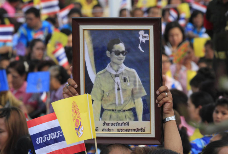 A person raises hight a portrait of Thai King Bhumibol Adulyadej upon of his arrival at a rice field in Ayutthaya province, central Thailand Friday, May 25, 2012. Thousands upon thousands of Thais turned out Friday in Bangkok and the historic capital Ayutthaya to show their devotion to the country's 84-year-old monarch on his first trip outside Bangkok in almost three years. (AP Photo)
