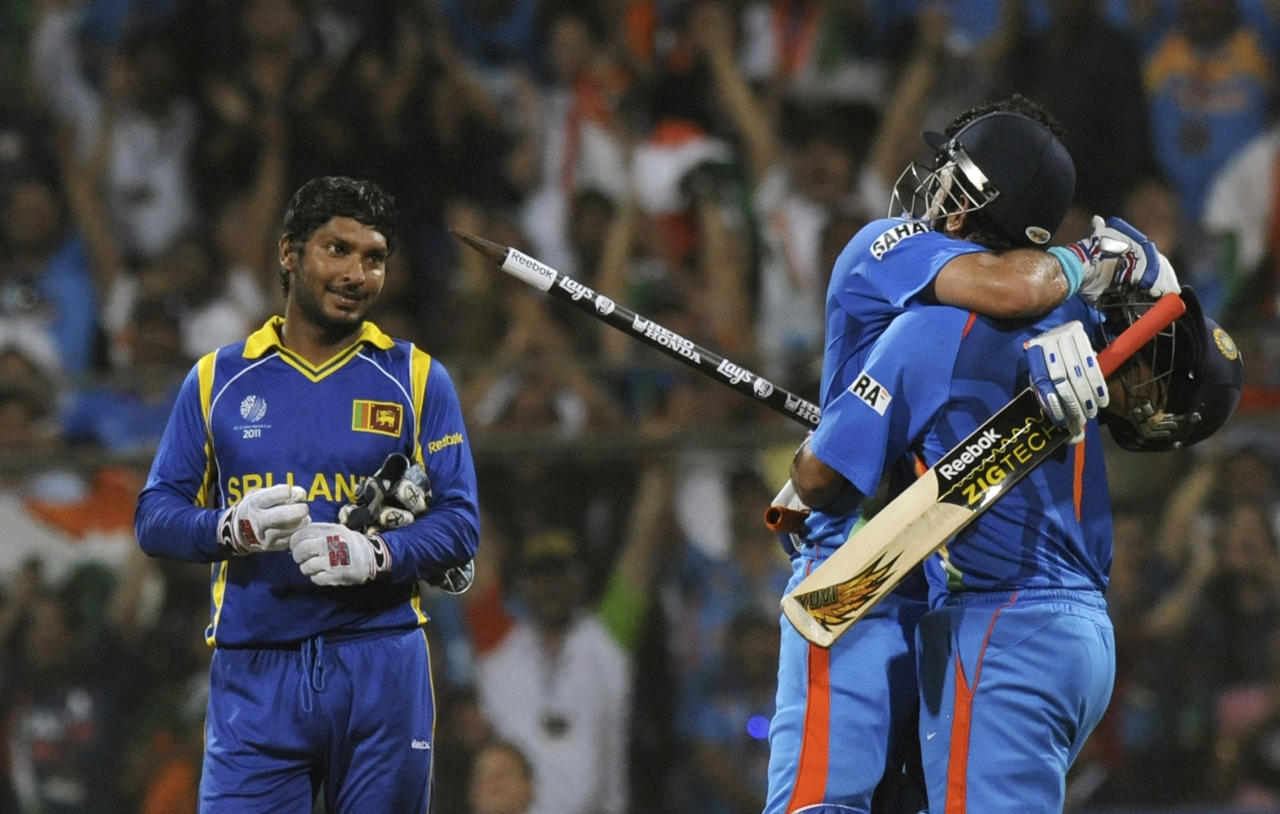 Defeated Sri Lankan captain Kumar Sangkkara (L) looks on as Indian captain Mahendra Singh Dhoni (C) and teammate Yuvraj Singh celebrate during their Cricket World Cup 2011 final at The Wankhede Stadium in Mumbai on April 2, 2011. India beat Sri Lanka by six wickets. AFP PHOTO/Indranil MUKHERJEE (Photo credit should read INDRANIL MUKHERJEE/AFP/Getty Images)