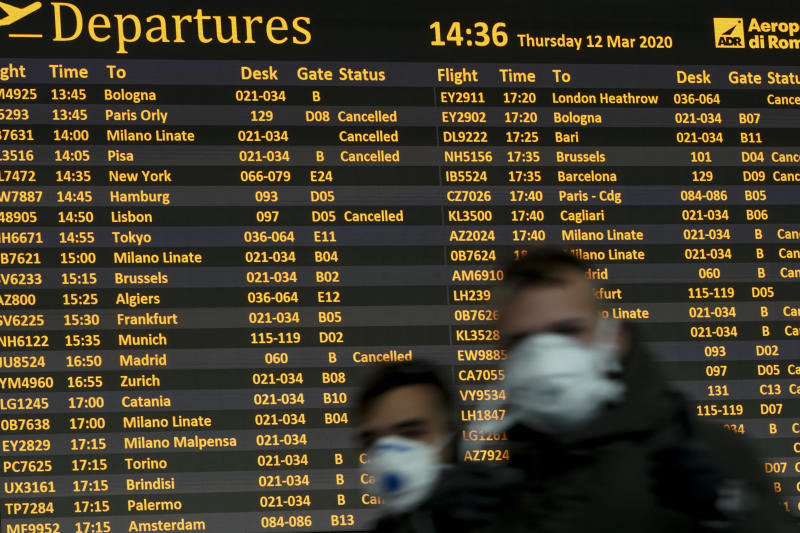 People walk by a departures monitor at the Rome Leonardo da Vinci International Airport, Thursday, March 12, 2020. Airlines and travelers are still sorting out the new travel ban that President Donald Trump announced late Wednesday, barring most foreign visitors from continental Europe for 30 days. (AP Photo/Andrew Medichini, File)