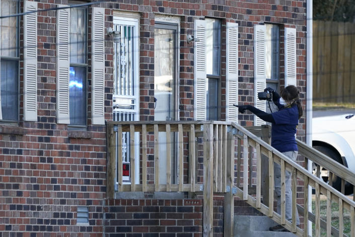 A member of the FBI Evidence Response Team photographs the entrance of a home Saturday, Dec. 26, 2020, in Nashville, Tenn. An explosion that shook the largely deserted streets of downtown Nashville early Christmas morning shattered windows, damaged buildings, and wounded three people. Authorities said they believed the blast was intentional. (AP Photo/Mark Humphrey)