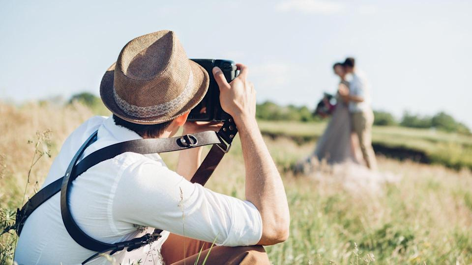 wedding photographer takes pictures of bride and groom in nature in summer, fine art photo.
