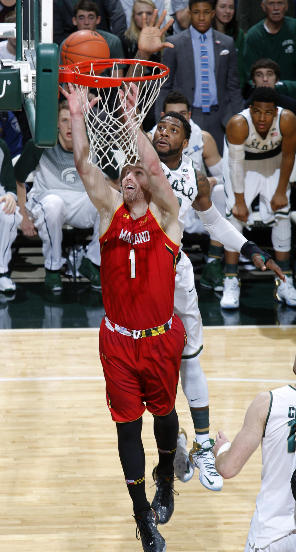 Maryland's Evan Smotrycz (1) shoots in front of Michigan State's Branden Dawson during the first half of an NCAA college basketball game, Tuesday, Dec. 30, 2014, in East Lansing, Mich. (AP Photo/Al Goldis)