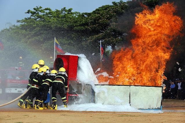 <p>Members of the Myanmar Fire Services Department participate in a fire drill during the Fire Service Department Day demonstration in Naypyitaw, Myanmar, May 5, 2017. (Photo: Hein Htet/EPA) </p>