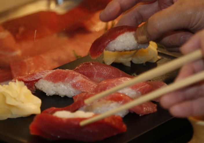 Customers take sushi of a bluefin tuna which was bought by sushi restauranteur Kiyoshi Kimura at the year's celebratory first auction, at his restaurant near Tsukiji fish market in Tokyo, Sunday, Jan. 5, 2014. Kimura paid 7.36 million yen (about $70,000) for the 507-pound (230-kilogram) bluefin tuna in the auction, just one-twentieth of what he paid a year earlier despite signs the species is in serious decline. (AP Photo/Shizuo Kambayashi)