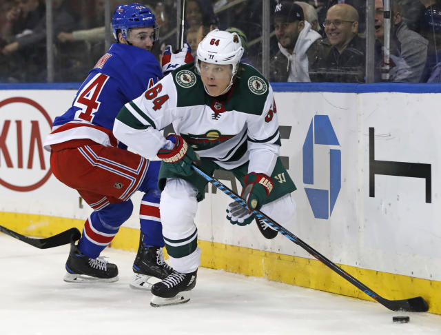 With New York Rangers defenseman Neal Pionk (44) looking on, Minnesota Wild right wing Mikael Granlund (64) looks to pass during the first period of an NHL hockey game in New York, Friday, Feb. 23, 2018. (AP Photo/Kathy Willens)