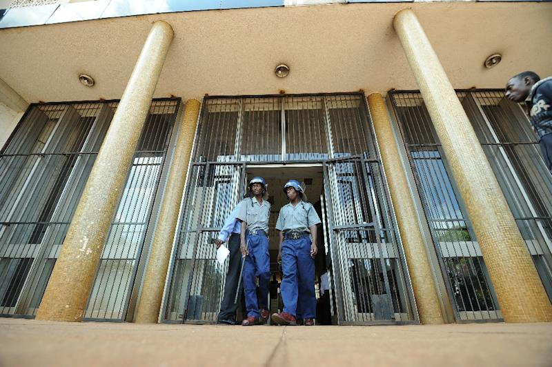 Zimbabwean riot police patrol outside Harare Magistrates Court on March 19, 2013
