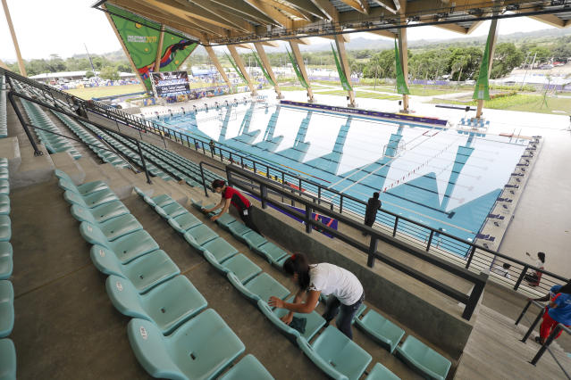 Workers clean the newly built Aquatics Center as they prepare for the 30th Southeast Asian Games at the New Clark City, Tarlac province, northern Philippines on Thursday Nov. 21, 2019. The country is hosting the SEA Games from Nov. 30-Dec. 12. (AP Photo/Aaron Favila)