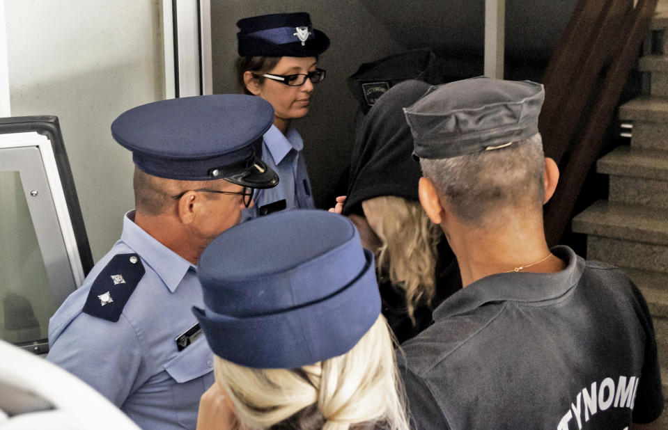 Police officers surround a British teenager accused of fasely claiming she was gang raped by Israeli tourists, as she leaves the Famagusta District Court in Paralimni in eastern Cyprus,on August 19, 2019 after her trial was postponed because of her request to be represented by a UK lawyer. - Initially, the 19-year-old woman had alleged that 12 Israelis gang raped her at the hotel where she was staying in the popular Ayia Napa resort on July 17. The young Israeli tourists were remanded in custody the next day. But hours before their second appearance in court five of them were released and sent home late the next day. (Photo by Iakovos Hatzistavrou / AFP)        (Photo credit should read IAKOVOS HATZISTAVROU/AFP via Getty Images)