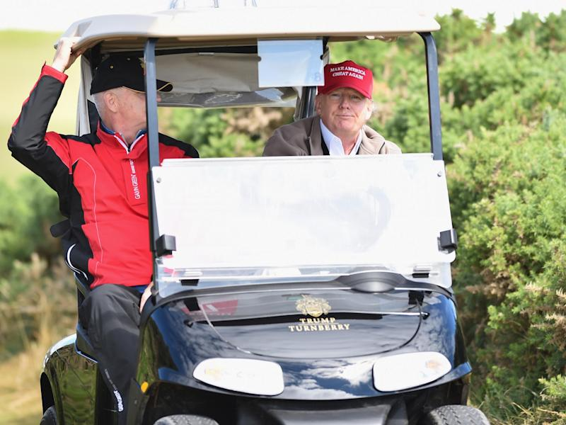 Donald Trump drives a golf buggy during his visits to his Scottish golf course Turnberry in 2016: Trump in a golf buggy during a visit to his Scottish golf course in 2016