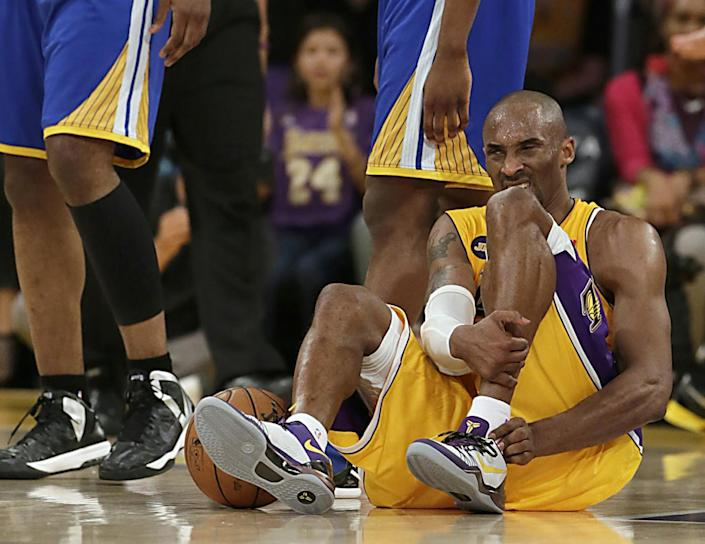Kobe Bryant writhes in pain after suffering a torn Achilles tendon during a game against the Warriors.