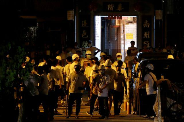 Men in white T-shirts and carrying poles are seen in Yuen Long after attacking anti-extradition bill demonstrators at a train station in Hong Kong, China, July 22, 2019.