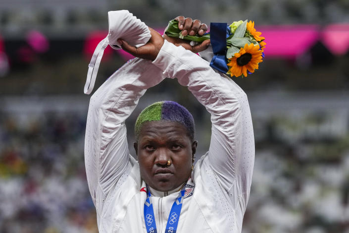 """Raven Saunders, of the United States, poses with her silver medal on women's shot put at the 2020 Summer Olympics, Sunday, Aug. 1, 2021, in Tokyo, Japan. During the photo op at her medals ceremony Sunday night, Saunders stepped off the podium, lifted her arms above her head and formed an """"X' with her wrists. Asked what that meant, she explained: """"It's the intersection of where all people who are oppressed meet."""" (AP Photo/Francisco Seco)"""