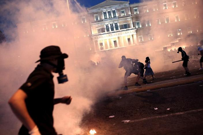 A protester clashes with riot police in front of the parliament in Athens on July 15, 2015 (AFP Photo/Angelos Tzortzinis)