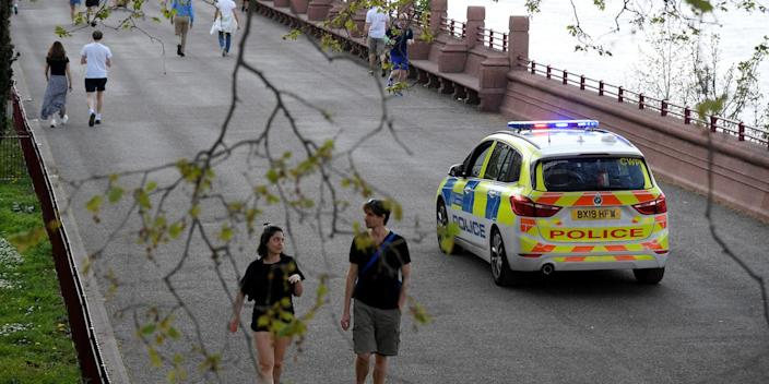 A police vehicle and people are seen in Battersea Park, as the spread of the coronavirus disease (COVID-19) continues, London, Britain, April 11, 2020.
