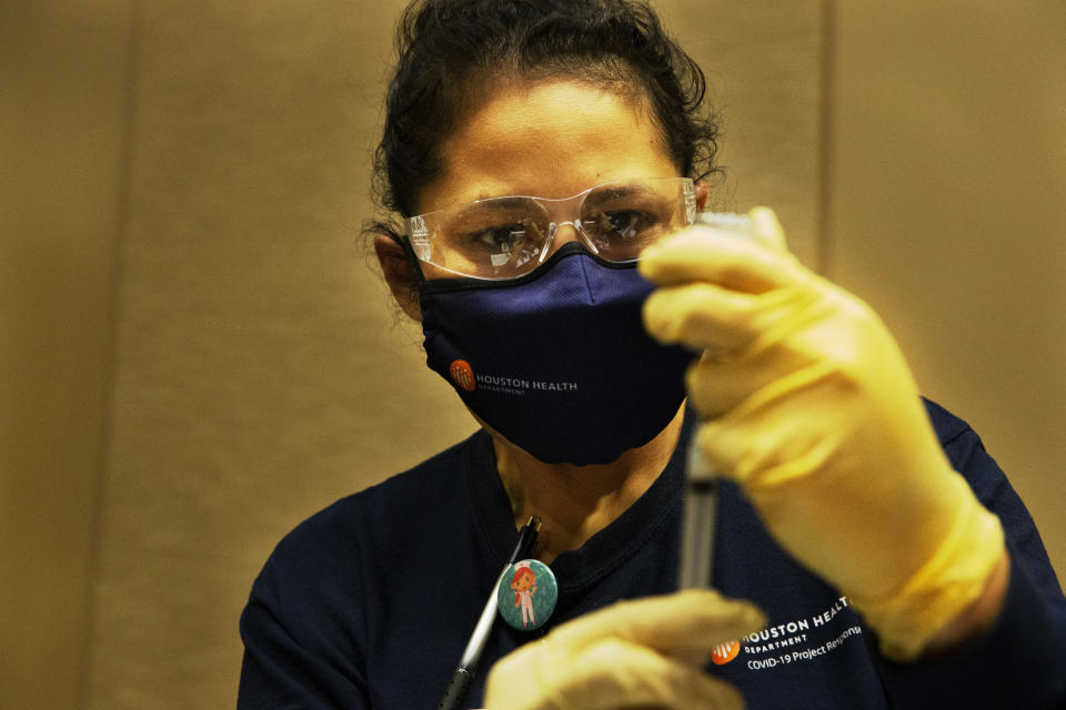 Houston Health Department LVN Alicia Meza prepares a dose of COVID-19 vaccine Sunday, Jan. 3, 2021, at a Houston Health Department's COVID-19 vaccine clinic in Houston. The department vaccinated 1,008 people who qualify under Phase 1A or Phase 1B of the state's guidelines at the clinic's first day on Saturday. (Yi-Chin Lee/Houston Chronicle via AP)