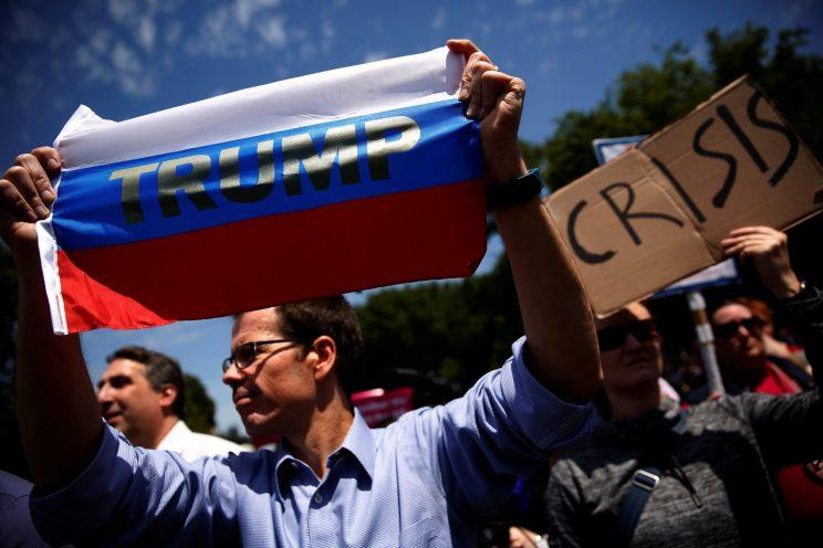 A protester holds a Russian flag with President Trump's name on it as demonstrators rally against Trump's firing of FBI Director James Comey, outside the White House