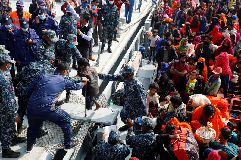 FILE PHOTO: Bangladesh Navy personnel help a disabled Rohingya refugee child to get off from a navy vessel as they arrive at the Bhasan Char island in Noakhali district