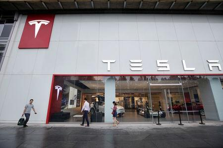 People walk past a showroom outside Tesla China headquarters in Beijing