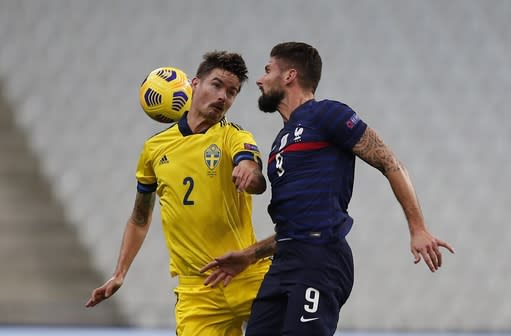 France's Olivier Giroud, right, and Sweden's Mikael Lustig jump for the ball during the UEFA Nations League soccer match between France and Sweden at the Stade de France stadium in Saint-Denis, northern Paris, Tuesday, Nov. 17, 2020. (AP Photo/Francois Mori)