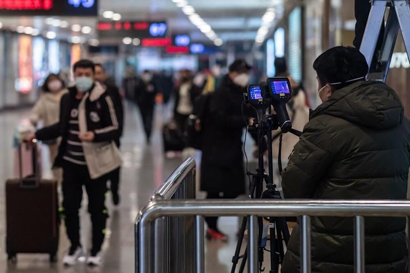 A workeroperates two advanced thermo camerasto check the body temperature of travelersat the arrival area of Beijing West Railway Station in Beijing.   NICOLAS ASFOURI/Getty Images