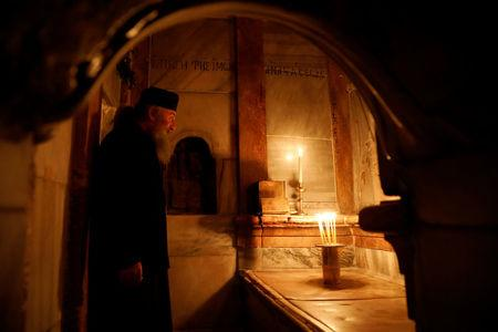 A Greek Orthodox priest stands inside the newly restored Edicule, the ancient structure housing the tomb (seen in front of him), which according to Christian belief is where Jesus's body was anointed and buried, at the Church of the Holy Sepulchre in Jerusalem's Old City March 20, 2017. REUTERS/Ronen Zvulun