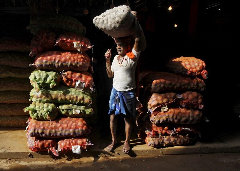 A labourer carries a sack of onions at a vegetable market in Kolkata
