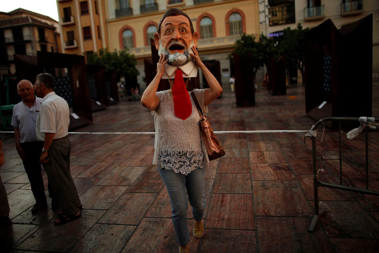 An activist of global anti-poverty charity Oxfam takes off a mask depicting Spanish Prime Minister Mariano Rajoy as she takes part in a protest as part of a campaign to denounce the non-fulfillment of the Spanish government's commitments to welcome refugees, in downtown Malaga, southern Spain June 20, 2017. REUTERS/Jon Nazca