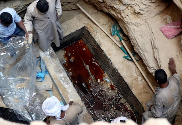Workersopen a coffin containing skeletal remainslying in sewage water in Alexandria, Egypt, on Thursday. (Mohamed Abd El Ghany / Reuters)