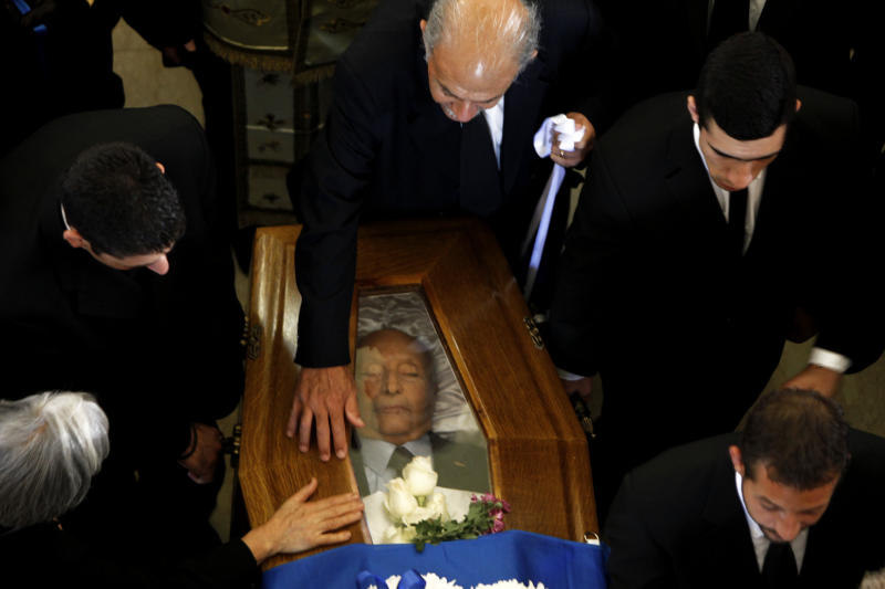 People touch the coffin of the former Cyprus President Glafcos Clerides during his funeral at the Orthodox Christian Church of the Lord's Wisdom in Nicosia, Cyprus, Tuesday, Nov. 19, 2013. Politicians, dignitaries, and hundreds of ordinary people gathered for the state funeral of Cyprus' former president, Glafcos Clerides, who died last week at the age of 94. (AP Photo/Petros Karadjias)
