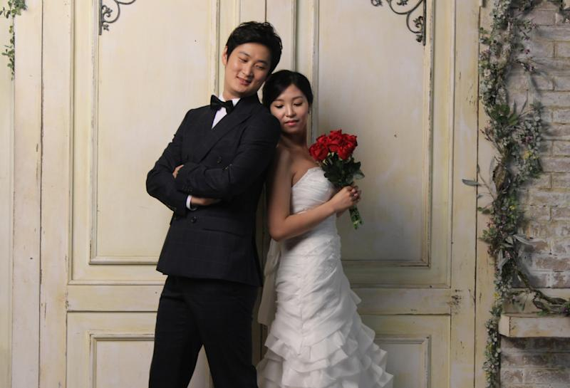 In this Tuesday, July 30, 2013 photo, Chen Jingjing, left, and Yang Candi of Beijing, China, strike a pose at a wedding studio in southern Seoul, South Korea, during an eight-hour photo session part of a South Korean wedding tourism package for Chinese couples. China is the source of one quarter of all tourists to South Korea, and a handful of companies in South Korea's $15 billion wedding industry are wooing an image-conscious slice of the Chinese jet set happy to drop several thousand dollars on a wedding album with a South Korean touch. (AP Photo/ Elizabeth Shim)
