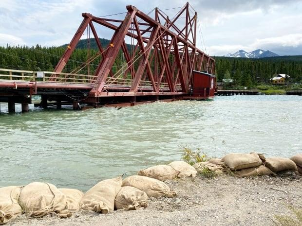 Water is touching the bottom of the White Pass and Yukon Route railway bridge in Carcross, pictured on Sunday. (Jane Sponagle/CBC - image credit)