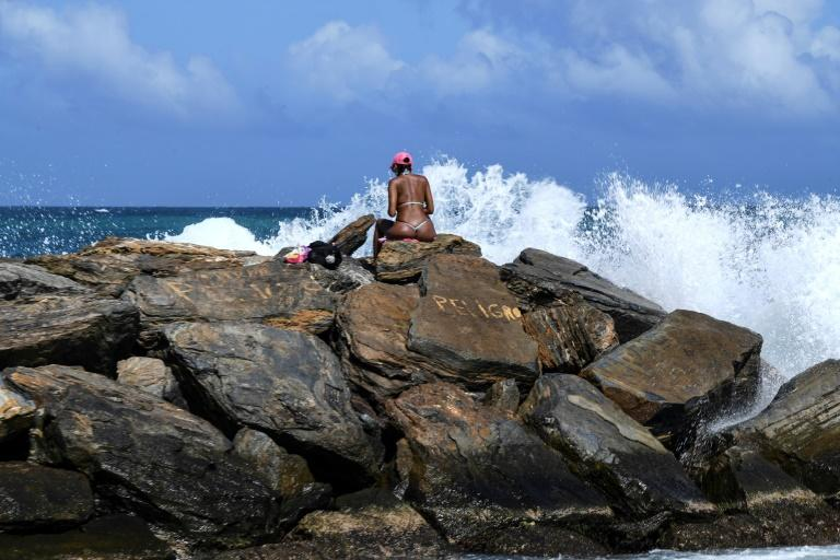 A woman sunbathes on the rocks at Camurichico beach in La Guaira, Vargas state, Venezuela (AFP Photo/Yuri CORTEZ)