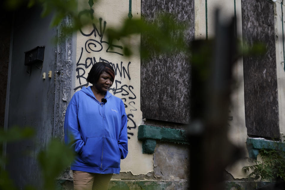 Pastor Marsha Hawkins-Hourd poses for a portrait outside a vacant building in St. Louis on Tuesday, May 18, 2021. She is part of a network of faith leaders and grassroots activists trying to overcome the distrust people have for the systems that typically address addiction but are infested with systemic racism, she said. She sees all the vacant buildings as a symbol of her neighbors who were deeply traumatized, then abandoned with limited access to treatment. (AP Photo/Brynn Anderson)