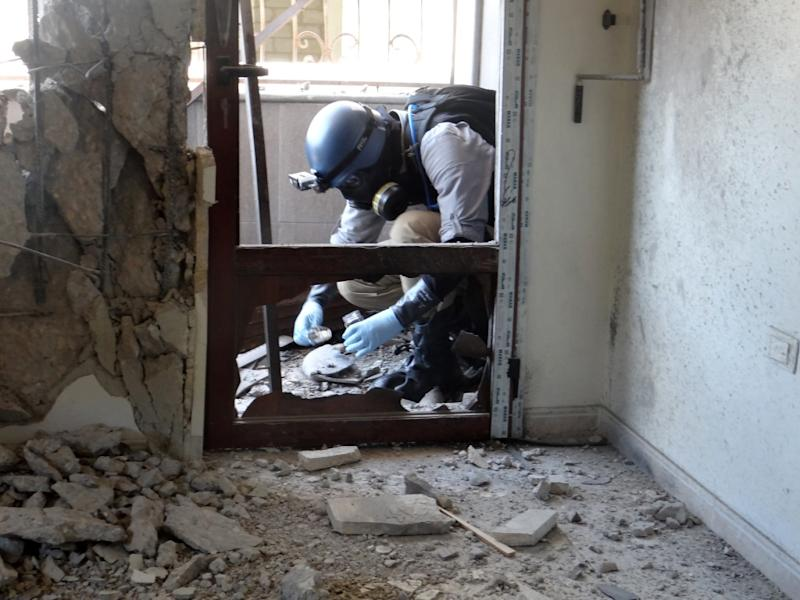 A United Nations arms expert collects samples on August 29, 2013, as they inspect the site where rockets had fallen in Damascus' eastern Ghouta suburb during an investigation into a suspected chemical weapons strike