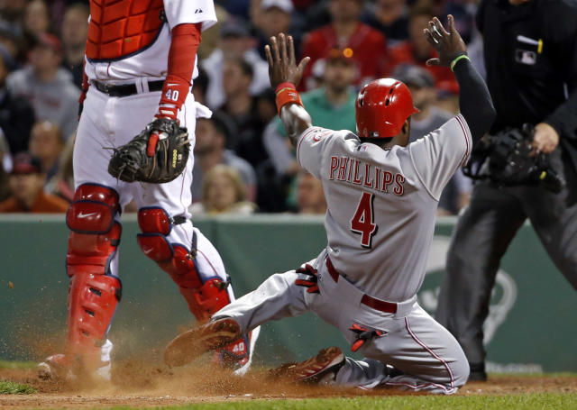 Cincinnati Reds' Brandon Phillips (4) slides into home to score on Ryan Ludwick's sacrifice fly as Boston Red Sox catcher A.J. Pierzynski (40) stands by during the eighth inning of a baseball game at Fenway Park in Boston, Tuesday, May 6, 2014. (AP Photo/Elise Amendola)