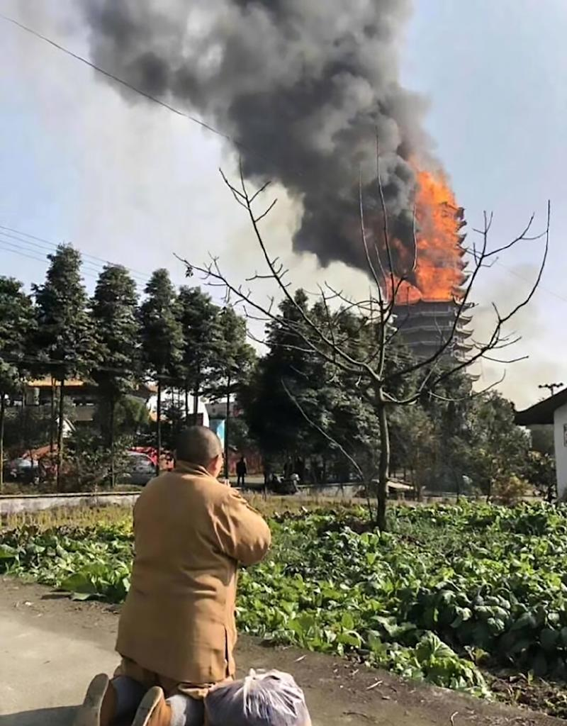 A Buddhist monk prays as the temple burns (Picture: Asia Wire)